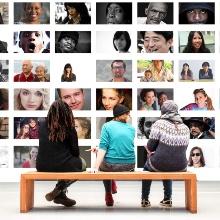 Menschen, die eine Wand mit Photos betrachten